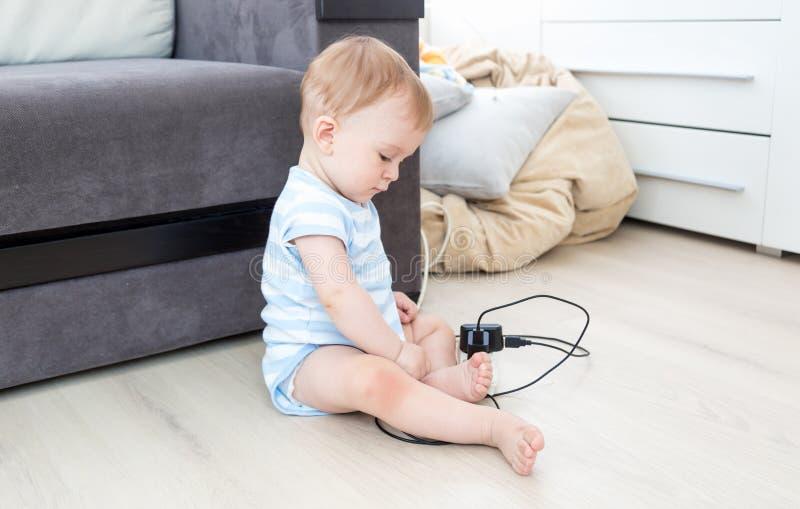 9 miesięcy starego chłopiec obsiadania na podłoga przy żywym pokojem i bawić się z drutami gniazdkowymi i elektrycznymi obrazy stock