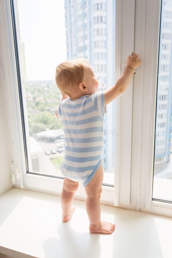 9 miesięcy starej chłopiec pozyci na windowsil i próbować otwierać kędziorek na okno i ciągnąć rękojeść obraz royalty free