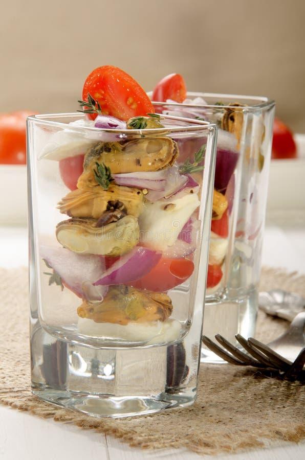 Miesmuschel mit lila Zwiebel und Tomate lizenzfreie stockfotos