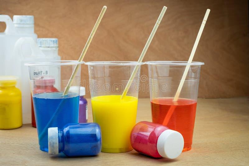 Mieszać koloru epoxy żywicę w plastikowej filiżance obraz royalty free