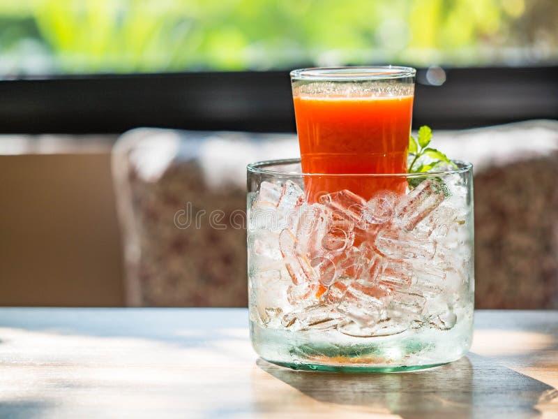 Miesza fruite sok w szkle z lodowym stawiającym dalej drewno stołem zdjęcie stock