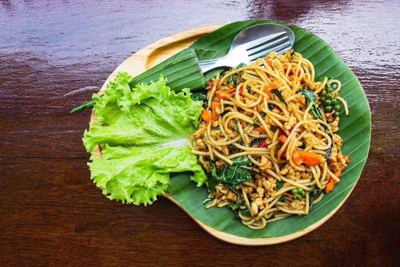 Miesza Smażącego spaghetti z warzywami i wieprzowiną w drewniany puchar stawiającym dalej tacy ciemnego brązu drewna stole Odg?rn obraz royalty free