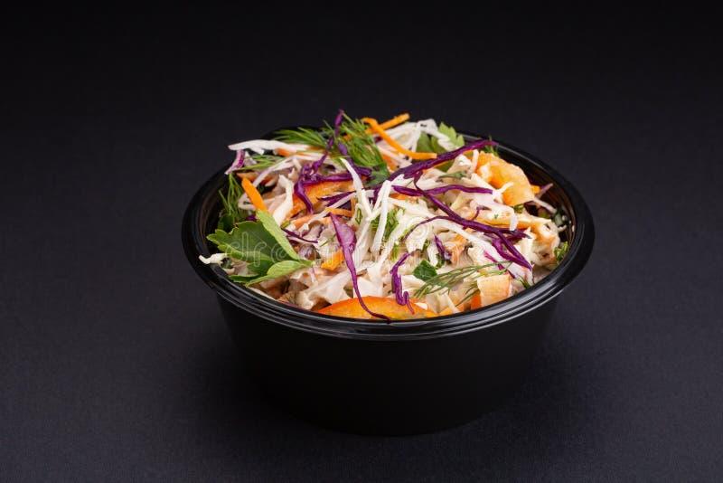 Miesza warzywa sałatkowych z purpurową kapustą, biała kapusta, sałata, marchewka w ciemnym glinianym pucharze na czarnym tle zdjęcie royalty free
