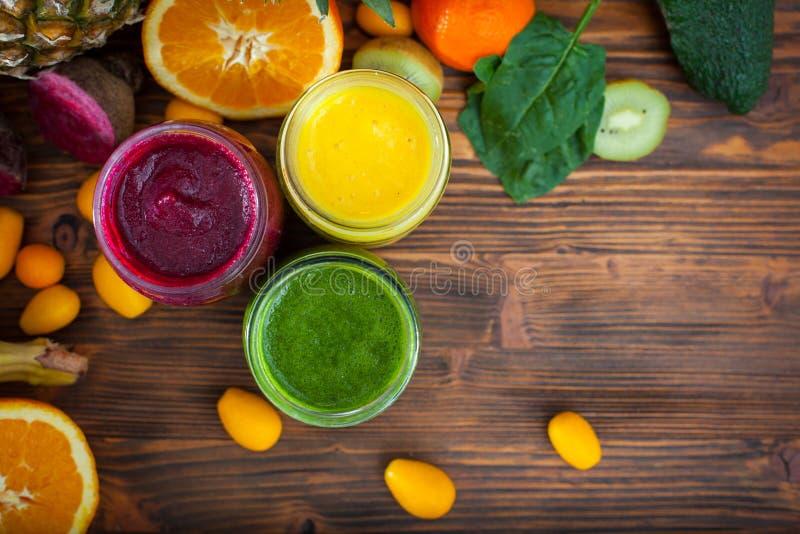 Mieszający zieleni, koloru żółtego i purpur smoothie z składnikami, obrazy royalty free