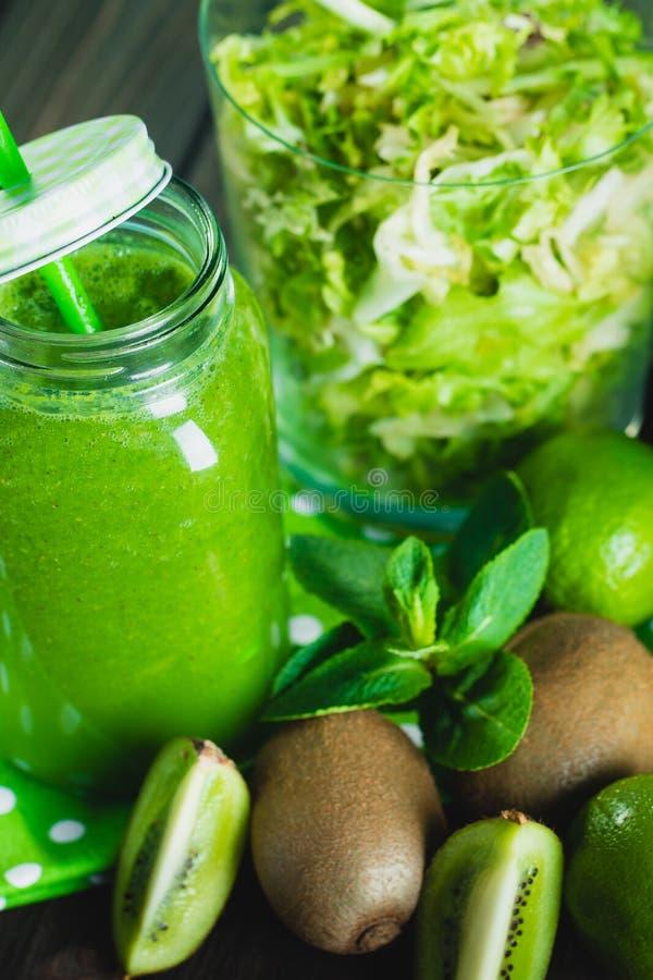 Mieszający zielony smoothie z składnikami na drewnianym stołowym selectiv obrazy stock