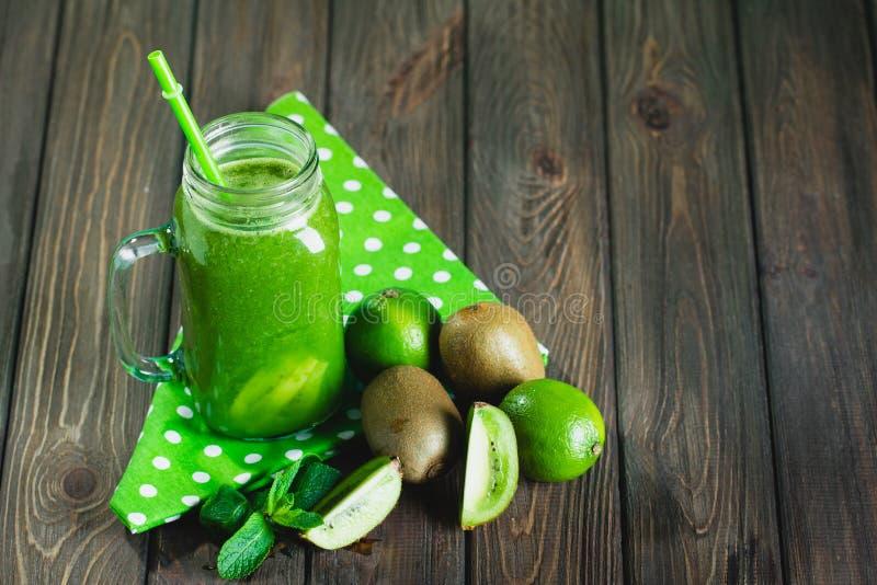 Mieszający zielony smoothie z składnikami na drewnianym stołowym selectiv zdjęcie royalty free