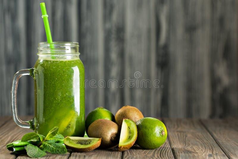 Mieszający zielony smoothie z składnikami na drewnianym stołowym selectiv fotografia royalty free