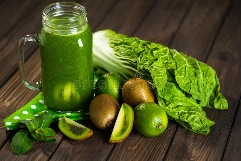 Mieszający zielony smoothie z składnikami na drewnianym stołowym selectiv zdjęcie stock