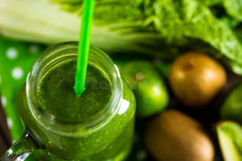 Mieszający zielony smoothie z składnikami na drewnianym stołowym selectiv obrazy royalty free