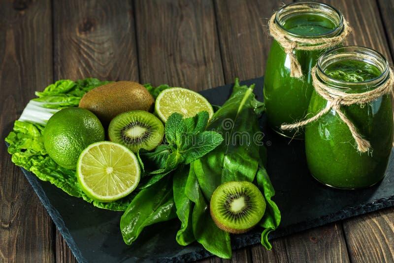 Mieszający zielony smoothie z składnikami na dryluje deskę, drewniany stół obrazy royalty free
