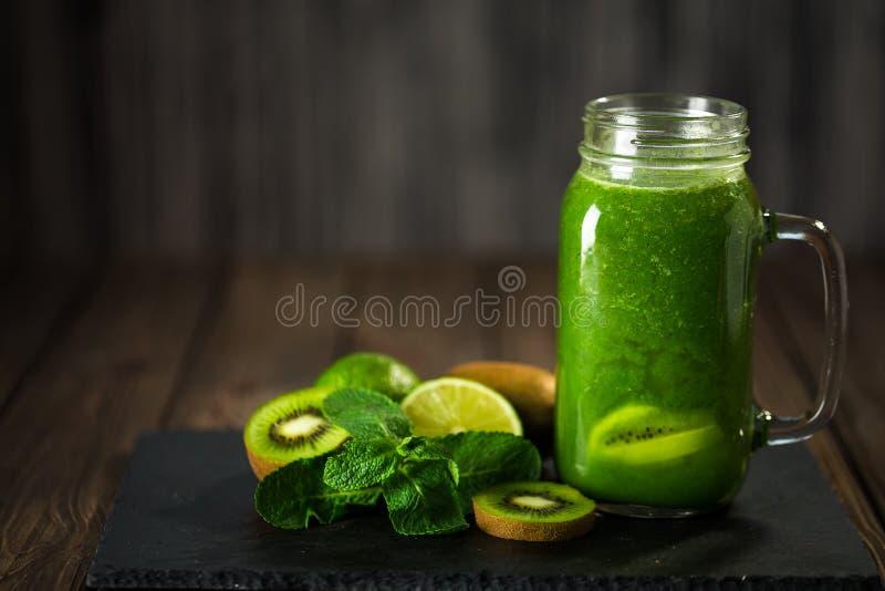 Mieszający zielony smoothie z składnikami na dryluje deskę, drewniany stół fotografia royalty free