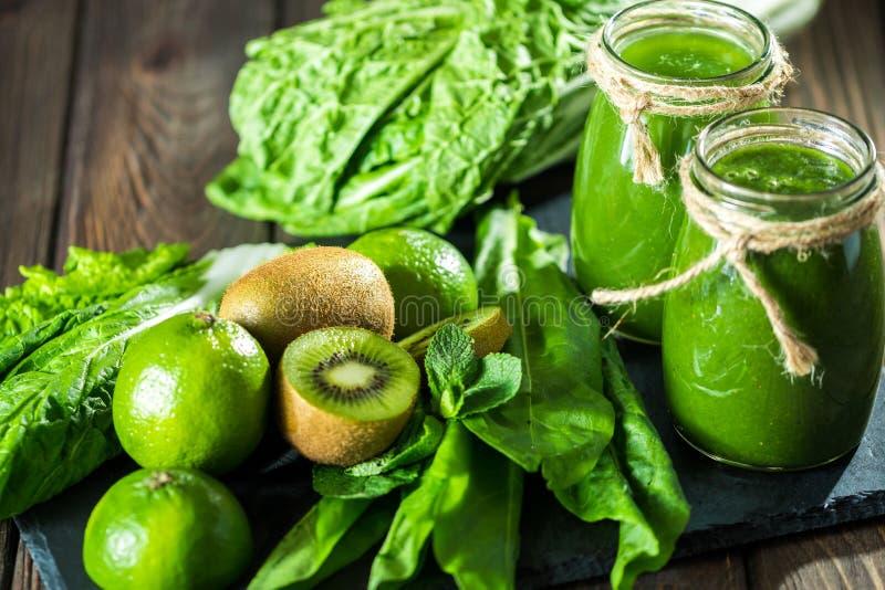 Mieszający zielony smoothie z składnikami na dryluje deskę, drewniany stół zdjęcie royalty free