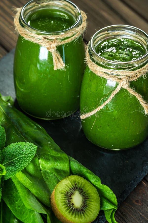 Mieszający zielony smoothie z składnikami na dryluje deskę, drewniany stół zdjęcia royalty free