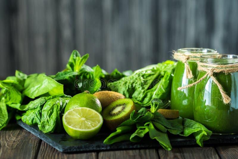 Mieszający zielony smoothie z składnikami na dryluje deskę, drewniany stół obraz royalty free