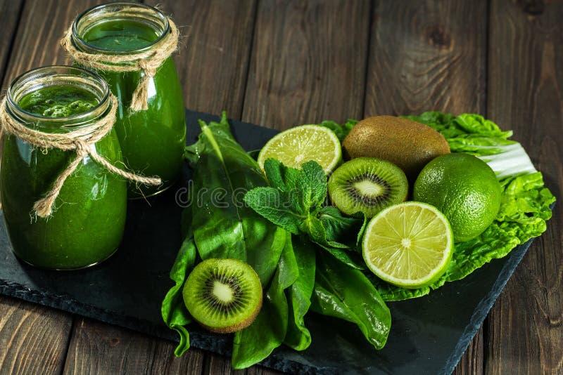 Mieszający zielony smoothie z składnikami na dryluje deskę, drewno obrazy royalty free