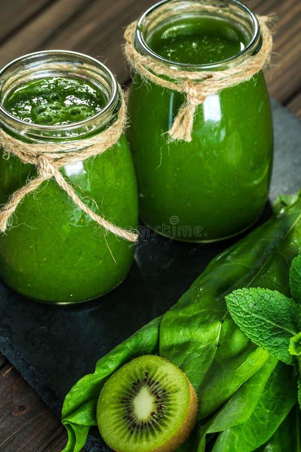 Mieszający zielony smoothie z składnikami na dryluje deskę, drewno zdjęcie stock