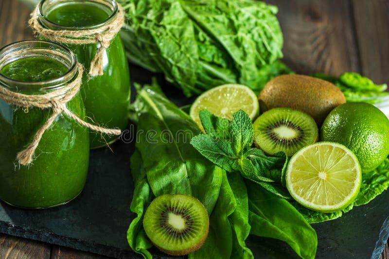 Mieszający zielony smoothie z składnikami na dryluje deskę, drewno zdjęcia royalty free