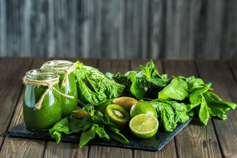 Mieszający zielony smoothie z składnikami na dryluje deskę, drewno zdjęcia stock