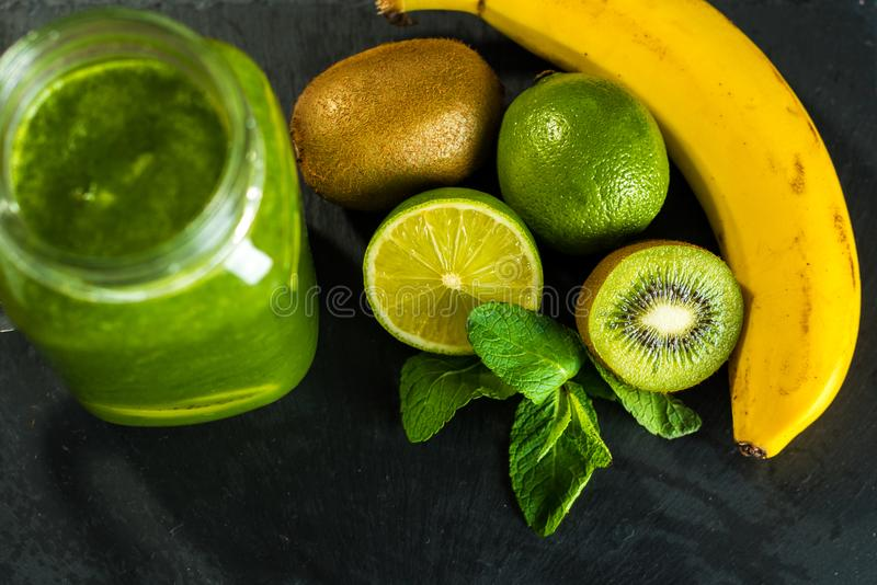 Mieszający zielony smoothie z składnikami na kamiennym drewnianym tabl zdjęcia royalty free