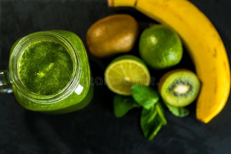 Mieszający zielony smoothie z składnikami na kamiennym drewnianym tabl zdjęcia stock