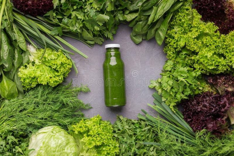 Mieszający zielony smoothie z składnikami na kuchennym stole obraz royalty free