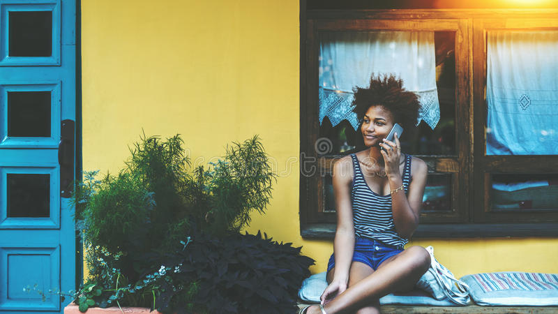 Mieszana śliczna dziewczyna z telefonem komórkowym sitiing blisko ściany obraz stock