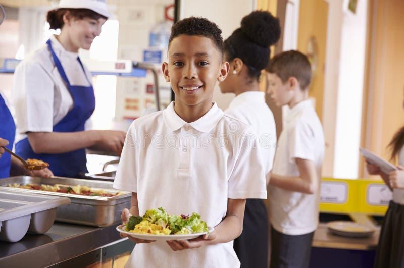 Mieszana biegowa chłopiec trzyma talerza jedzenie w szkolnym bufecie obraz stock