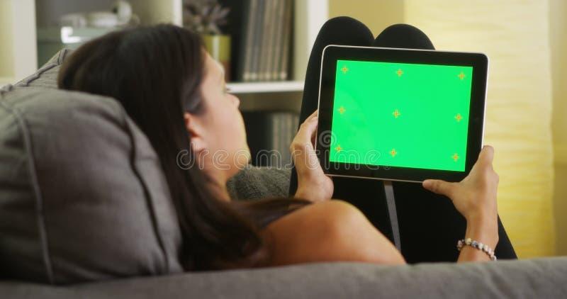 Mieszana biegowa dziewczyna patrzeje pastylkę z zieleń ekranem zdjęcia stock