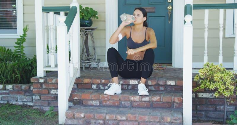 Mieszana biegowa kobieta odpoczywa w domu i woda pitna zdjęcie royalty free