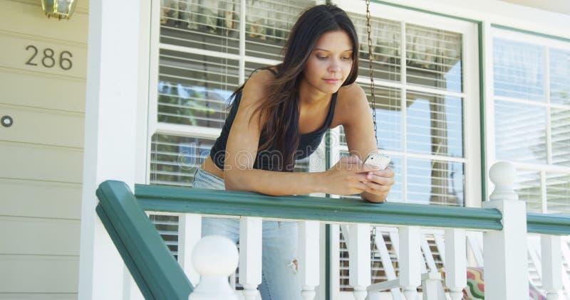 Mieszana biegowa kobieta opiera na sztachetowy texting fotografia royalty free