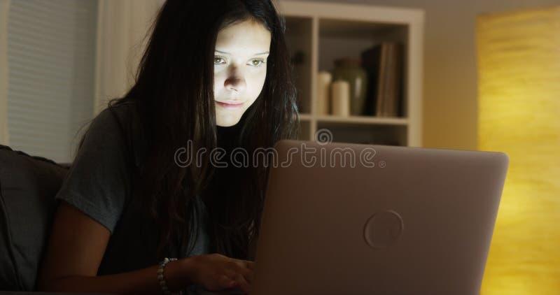 Mieszana biegowa kobieta używa laptop przy nocą obrazy royalty free