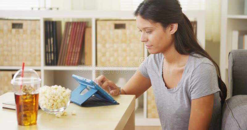 Mieszana biegowa kobieta używa pastylkę na stolik do kawy obraz stock