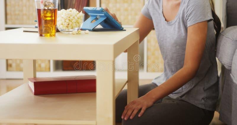 Mieszana biegowa kobieta używa pastylkę na stolik do kawy zdjęcie royalty free