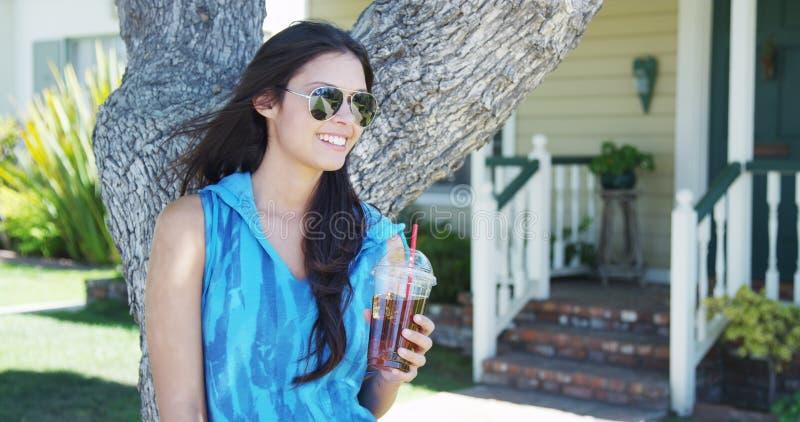 Mieszana biegowa kobiety pozycja drzewem pije lukrowej herbaty obraz stock