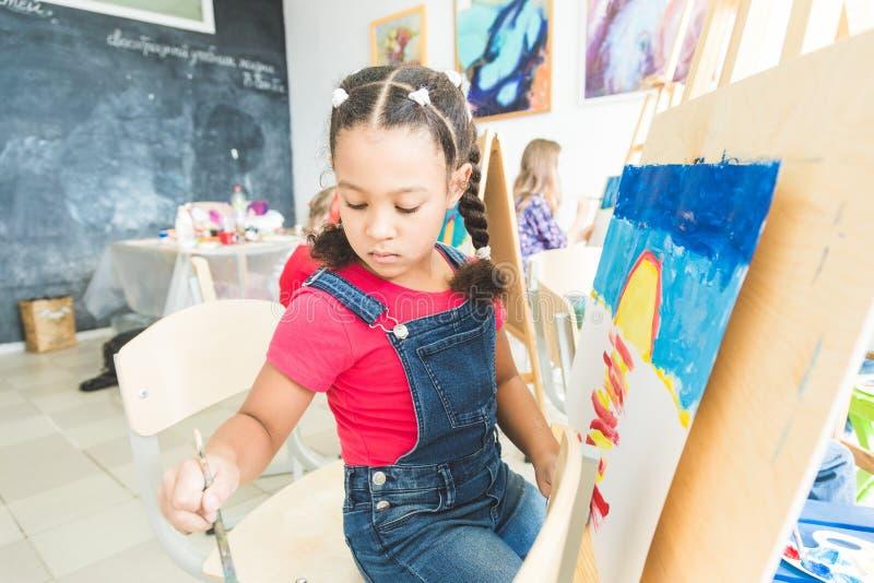Mieszana biegowa mała dziewczynka z nauczycielem w grupie preschool uczeń siedział rysunek obrazek Malować na maelbert obrazy royalty free