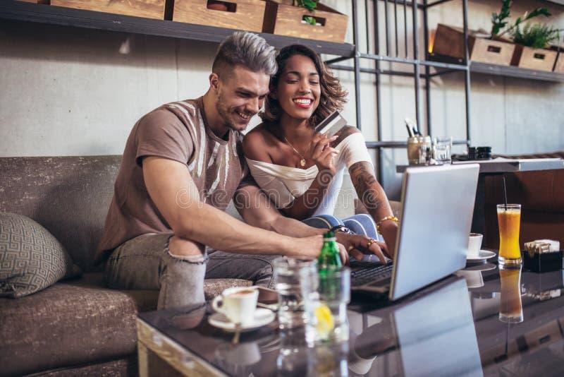 Mieszana biegowa para kupuje online z kredytową kartą i laptopem w kawiarni zdjęcia royalty free