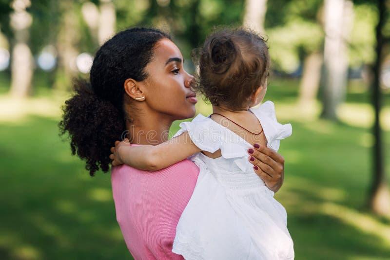 Mieszana kobieta wyścigu trzyma swoją małą córkę obrazy stock