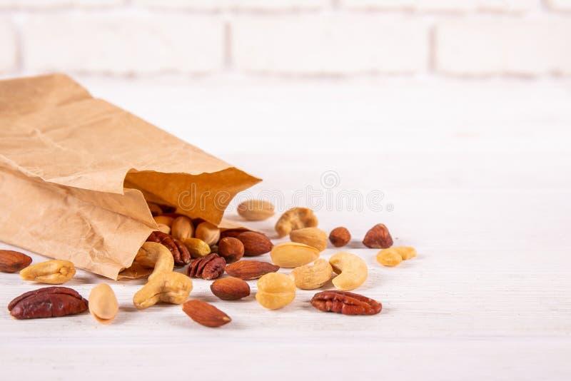 Mieszane dokrętki w drewnianym pucharze i rozpraszać na stole Wlec mieszankę pecan, migdał, macadamia & Brazil jadalne dokrętki z zdjęcie stock