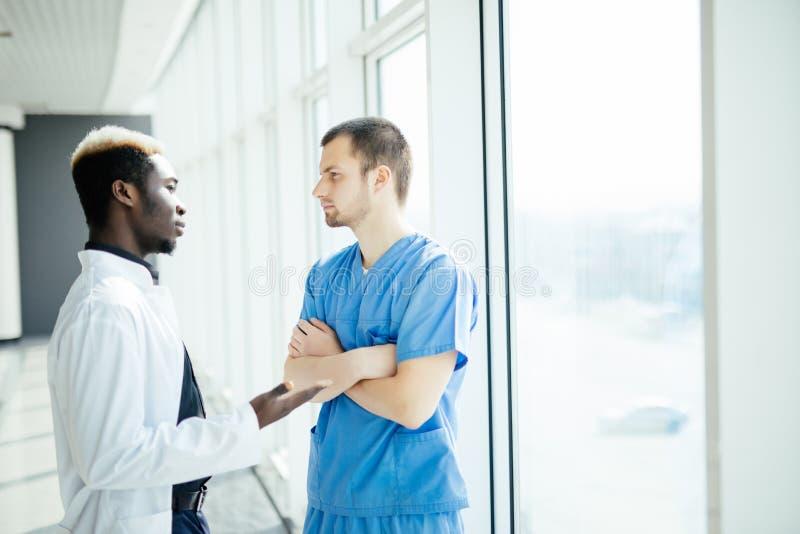 Mieszane rasy Dwa lekarki dyskutuje rezultaty analiza w nowożytnym szpitalu zdjęcie stock