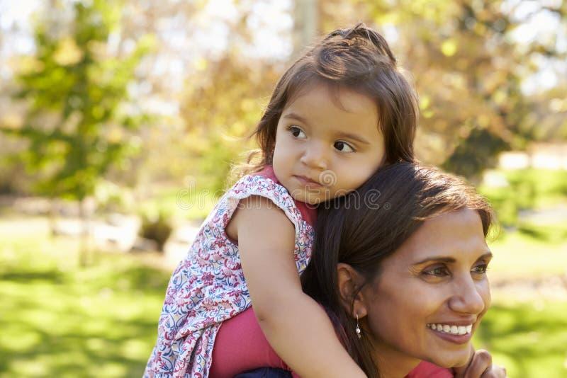 Mieszanego rasy matki przewożenia młoda córka na ona ramiona fotografia royalty free