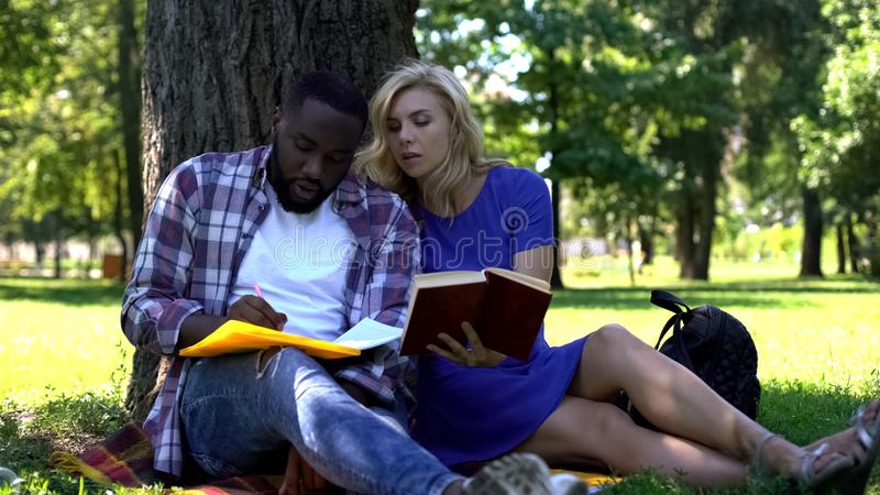 Mieszani ścigający się ucznie robi notatkom i patrzeje w książce, uniwersytecki projekt obraz stock