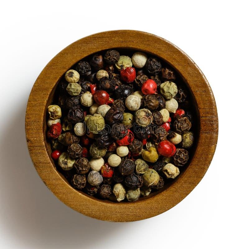Mieszani peppercorns w ciemnym drewnianym pucharze odizolowywającym na bielu fotografia royalty free