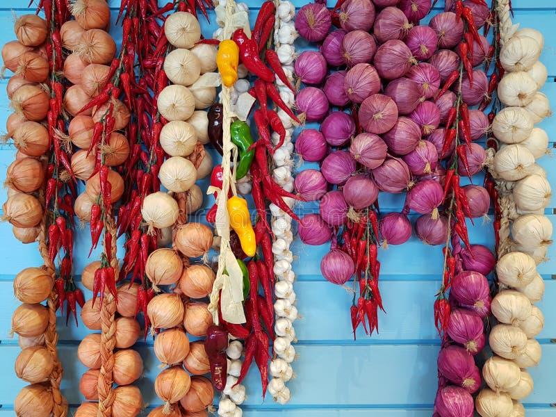 Mieszani ziele Chillies, cebule i garlics, wieszają na nieba błękita drewnianym tle szef kuchni pojęcia karmowa świeża kuchni ole zdjęcia stock