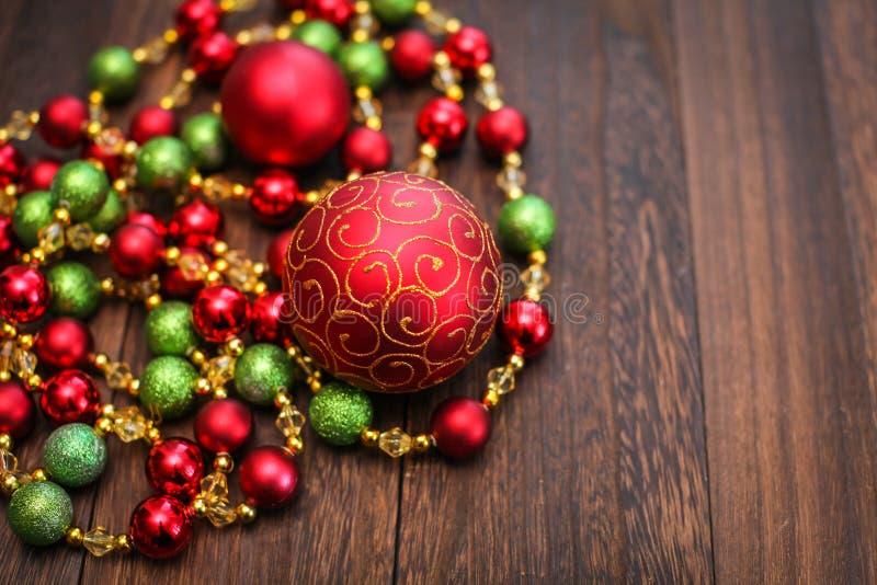 Mieszanka czerwień, zieleń i złote Bożenarodzeniowe piłki, Nowego Roku wystrój dla drzewa na ciemnym drewnianym tle obrazy stock