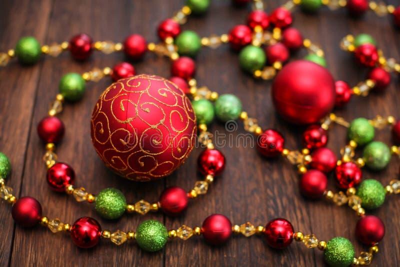 Mieszanka czerwień, zieleń i złote Bożenarodzeniowe piłki, Nowego Roku wystrój dla drzewa na ciemnym drewnianym tle obrazy royalty free