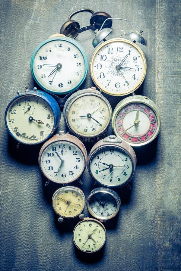 Mieszanka starzy zegary w stosie w drewnianym stole fotografia stock