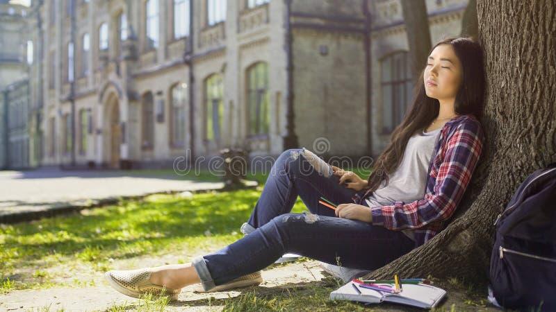 Mieszany żeński relaksować pod drzewem z oczami zamykającymi, stresujący dzień, peacefulness zdjęcia stock