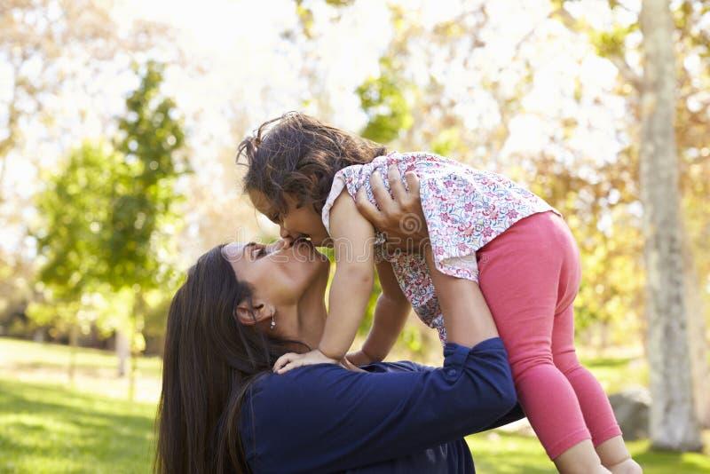 Mieszany biegowy Azjatycki mum całuje jej młodej córki w parku obrazy royalty free