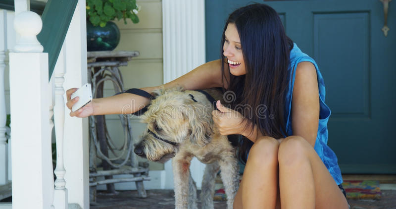 Mieszany biegowy kobiety obsiadanie na ganeczku bierze obrazki z psem obraz stock
