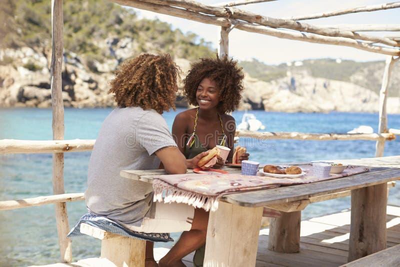 Mieszany biegowy pary łasowanie przy stołem morzem, Ibiza, Hiszpania zdjęcie royalty free